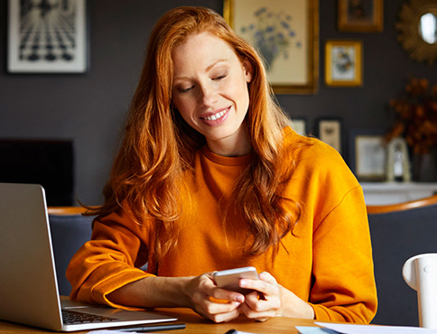 Woman with cell phone and laptop