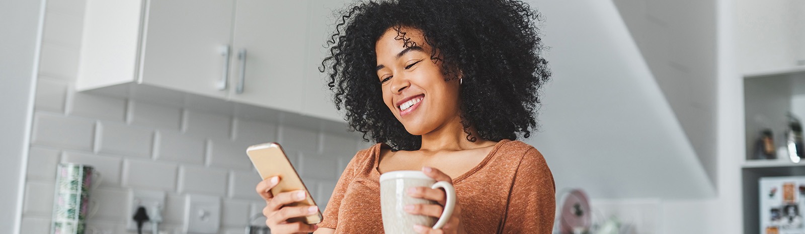 Woman on a cell phone holding a coffee